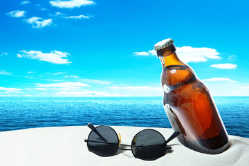 Bottle beer and sunglasses in the sand of a tropical beach