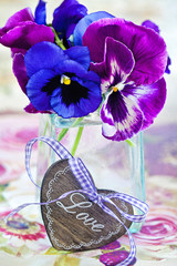 Photo of a beautiful purple pansy flowers and wooden heart.
