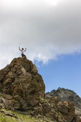 Ragazzo con braccia in alto in montagna