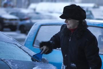 Mature woman in a coat scraping windows