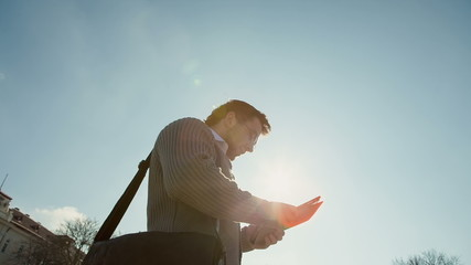 A young businessman with a tablet on a background of the sun's