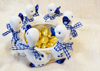 Chocolate Easter eggs in white with blue vase with ducks figures