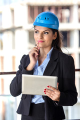 Young female architect working at construction site.