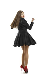 Attractive happy woman in black dress spinning on red high heels