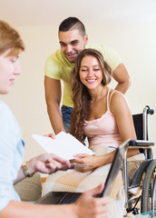 Happy couple with disabled wife talking with  banking clerk