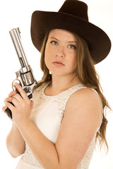 cowgirl holding revolver with serious facial expression looking