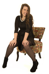 Happy female model sitting in a floral chair