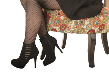 Legs and feet of a woman sitting in floral chair with high heels