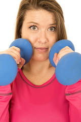 Scary expression of a young woman holding blue barbells