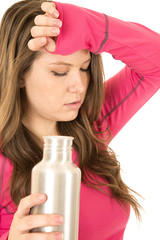 Exhausted female fitness model holding a stainless steel water b