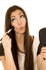 Beautiful teen girl pulling funny face applying blush