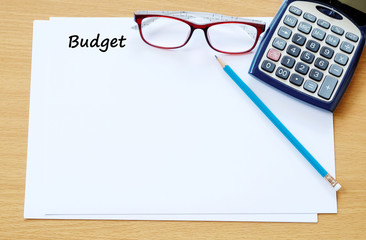Budget word on paper with calculator and glasses background, fin