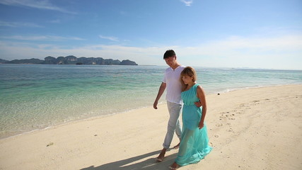 handsome man walk with asian blonde girl in blue dress on sandy