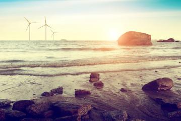 white wind turbine generating electricity on sea