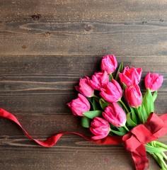 Pink tulips bouquet on dark wood background