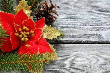 Christmas flower red with bows on a wooden board