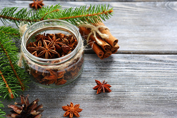 Aromatic anise in jar with pine branches on the boards