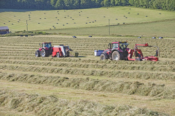 Tractors and bale wrapper baling hay in field