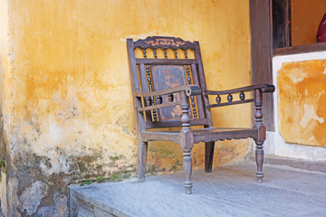 old wooden chair against a background of yellow wall, Vietnam, H