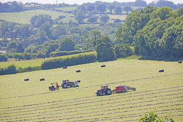 Tractors and bale wrapper baling hay in field, Dorset, UK