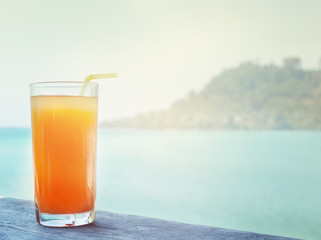 glass of orange juice on the background of the sea background