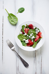 Salad with spinach, strawberry and cheese, white wooden surface