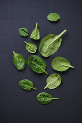 Above view of spinach leaves over black wooden surface