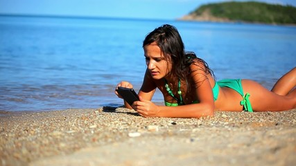 Pretty woman using and talking her phone on the beach. Koh Samui