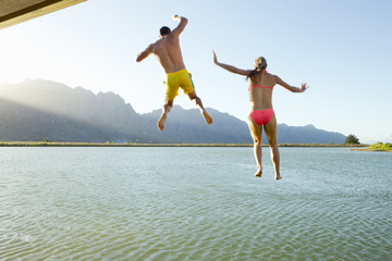 Couple in swimwear, jumping into a lake from a jetty