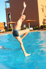 preteen little boy jump into open air swimming pool
