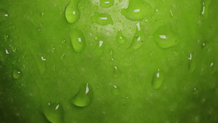 Drops of water flow down along the surface of a green apple