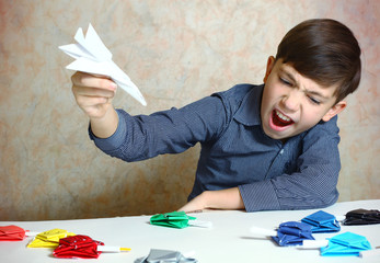 creative handsome preteen boy make origami tanks and plain  from