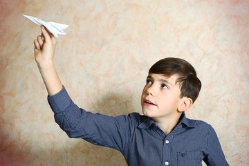 preteen handsome boy play with origami paper plain