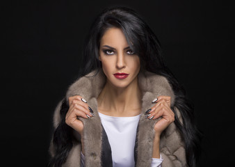 portrait of a beautiful brunette in a fur coat