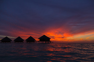 Sunset in the Maldives with a view of the lagoon and bungalows
