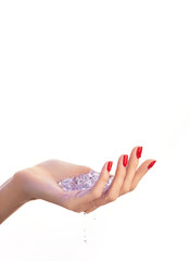 Female hand with red nail design and ice cubes inside