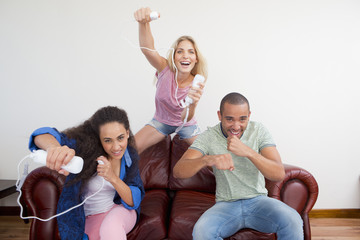 Three friends playing video game on sofa