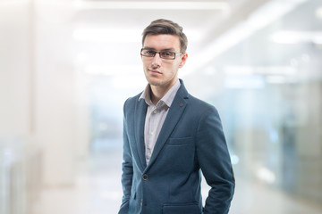 Young confident businessman standing in the office with serious