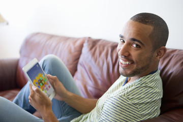 Man relaxing on sofa with a digital tablet