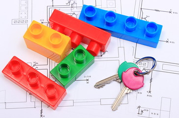Home keys and building blocks on construction drawing of house