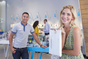 Woman with purchase in phone store