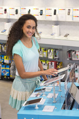 Woman browsing digital tablets in phone store