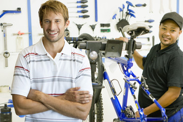 Portrait of store manager and cycle technician in workshop