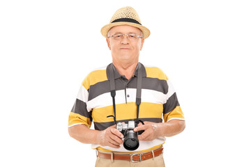 Mature tourist holding a camera and posing