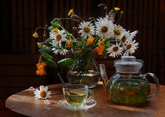Tea with a camomile and a bouquet in a transparent jug