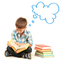 Cute little boy dreaming about something while reading book