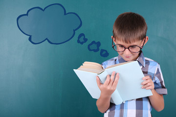 Schoolboy at blackboard in classroom and text cloud with space