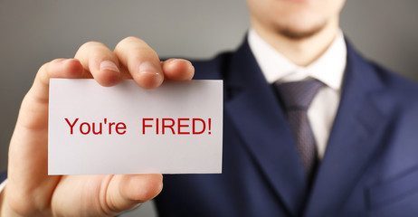Businessman holding card with text You are fired