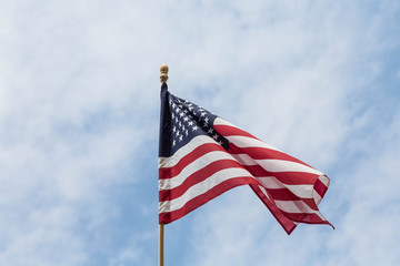 American Flag on Wood Pole Against Sky