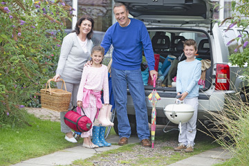 Grandparents and grandchildren packing car for vacation